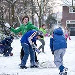 Kinderen houden sneeuwballen gevechten op straat