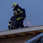 Vlammen slaan uit schoorsteen Elzenplein in Haarlem