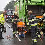 Vuilnisman zit met hand klem in vuilniswagen op de Kleverlaan in Haarlem