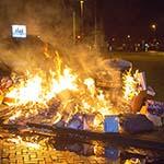 Papierberg naast gesloten container in de brand gestoken