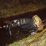 Auto glijdt in het water langs de Haarlemmerstraatweg in Haarlem