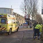 Fietsster valt midden op de spoorwegovergang op de Westergracht