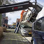 Vuilniswagen waait op geparkeerde auto's in Haarlem
