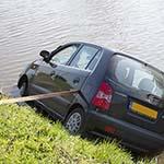 Auto te water langs de Middenweg in Halfweg