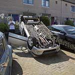 Auto op zijn dak bij inparkeren in Velserbroek