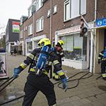 Prullenbak in de brand in winkelpand in Haarlem